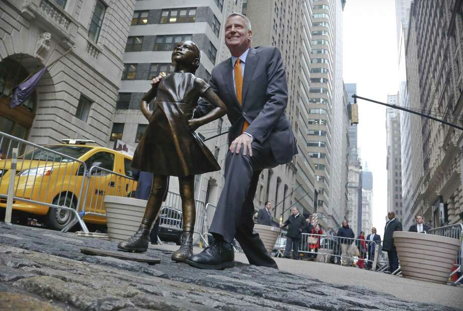 "New York Mayor Bill de Blasio poses with the ""Fearless Girl"" statue before holding a news briefing Monday. De Blasio says the popular statue will be allowed to remain through February 2018. Photo: Bebeto Matthews /Associated Press / Copyright 2017 The Associated Press. All rights reserved."