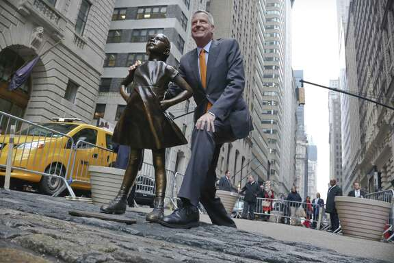 """New York Mayor Bill de Blasio poses with the """"Fearless Girl"""" statue before holding a news briefing Monday. De Blasio says the popular statue will be allowed to remain through February 2018."""