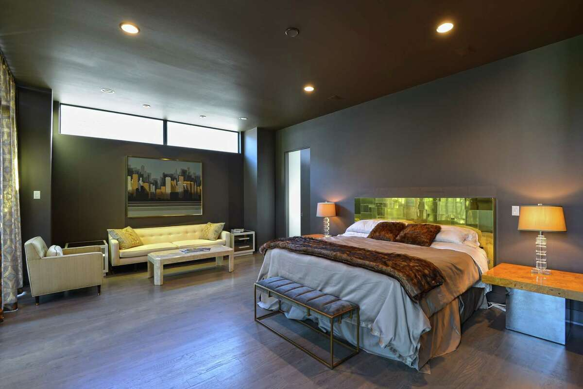 Dark grayish bluepaint sets a dramatic tone in the master bedroom, which holds more original mid-century design.