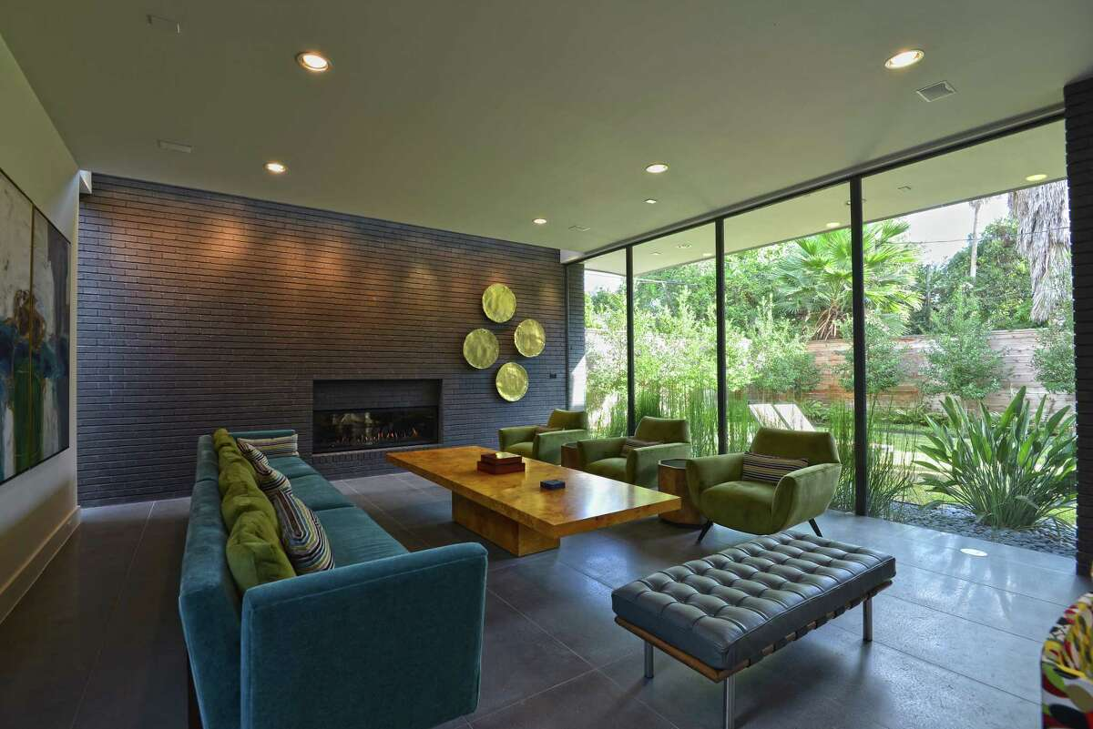 The living room has a wide view of the backyard, and the room is filled with original midcentury pieces such as the Milo Baughmann coffee table and the 1950's-era Edward Wormley sofa that's been reupholstered.