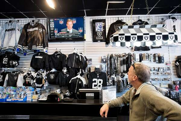 Andy Chose of Walnut Creek watches an NFL press conference while shopping at Raider Image on Monday, March 27, 2017, in Oakland, Calif., shortly after the NFL approved the team's move to Las Vegas.