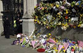 Floral tributes to the victims of the Westminster terrorist attack placed outside the Palace of Westminster, London, Monday March 27, 2017. Attacker Khalid Masood is believed to have used the messaging service WhatsApp before running down pedestrians on Westminster Bridge and storming a gate outside Parliament armed with two knives, Wednesday. Four died in the rampage, including a police officer. (AP Photo/Matt Dunham)