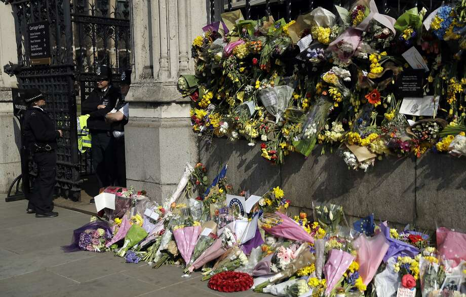 Floral tributes to the victims of the Westminster terrorist attack placed outside the Palace of Westminster, London, Monday March 27, 2017. Attacker Khalid Masood is believed to have used the messaging service WhatsApp before running down pedestrians on Westminster Bridge and storming a gate outside Parliament armed with two knives, Wednesday. Four died in the rampage, including a police officer. (AP Photo/Matt Dunham) Photo: Matt Dunham, Associated Press