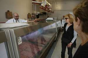 David Samiljan (left), owner Baron's Meats of Alameda, talks with Kay Harnich-Ladd (second from right) talk at  Baron's Meats of Alameda on Church Street as Samijan prepared the store for its opening on  Monday, March 27, 2017 in San Francisco, Calif.