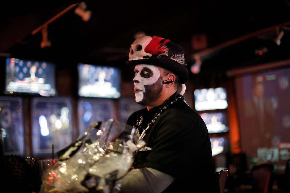 Michael Lambirth, aka VooDoo Man, is surrounded by the news of the Raiders imminent departure as it was announced on multiple screens at Ricky's Sports Theater and Grill in San Leandro, Calif., on Monday, March 27, 2017. The NFL announced that team owners had approved the Raiders' move to Las Vegas.