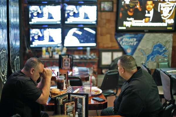 Rob Rivera, president of the Black Hole, and Ray Bobbitt, with the Oakland Coliseum Economic Impact Committee, listen to the news of the Raiders imminent departure at Ricky's Sports Theater and Grill in San Leandro, Calif., on Monday, March 27, 2017. The NFL announced that team owners had approved the Raiders' move to Las Vegas.