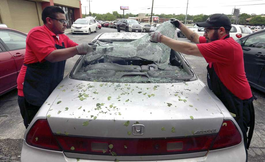 Safelite automotive glass repair company employees remove broken glass last year after a widespread overnight hailstorm broke windshields throughout large swaths of the city. That storm and others weighed on USAA's bottom line, leading to its lowest profit since the Great Recession. Photo: William Luther /San Antonio Express-News / © 2016 William Luther