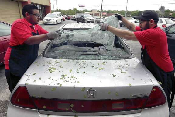 Safelite automotive glass repair company employees remove broken glass last year after a widespread overnight hailstorm broke windshields throughout large swaths of the city. That storm and others weighed on USAA's bottom line, leading to its lowest profit since the Great Recession.