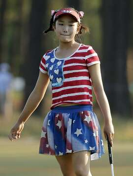 Lucy Li reacts to her putt on the 11th hole during the first round of the U.S. Women's Open golf tournament in Pinehurst, N.C., Thursday, June 19, 2014. (AP Photo/Chuck Burton)