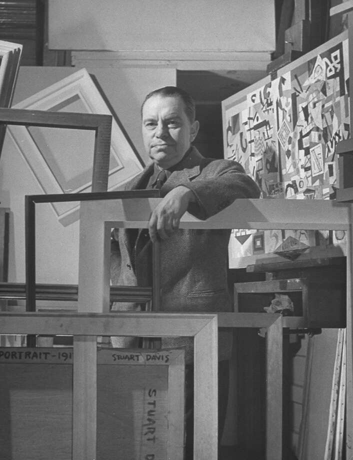 "Davis' signature is a meandering visual element in ""Blips and Ifs,"" left, finished in 1964, the year of the artist's death. Davis, shown in his studio, right, was so committed to his ideas that he often reworked canvases over many years. Photo: Ralph Morse, The LIFE Picture Collection/Getty Images"
