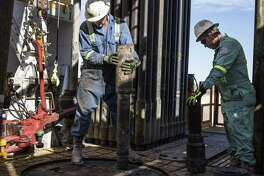 Precision Drilling oil rig operators install a bit guide on the floor of a Royal Dutch Shell Plc oil rig near Mentone, Texas, U.S., on Thursday, March 2, 2017. Exxon Mobil Corp., Royal Dutch Shell and Chevron Corp., are jumping into American shale with gusto, planning to spend a combined $10 billion this year, up from next to nothing only a few years ago. Photographer: Matthew Busch/Bloomberg
