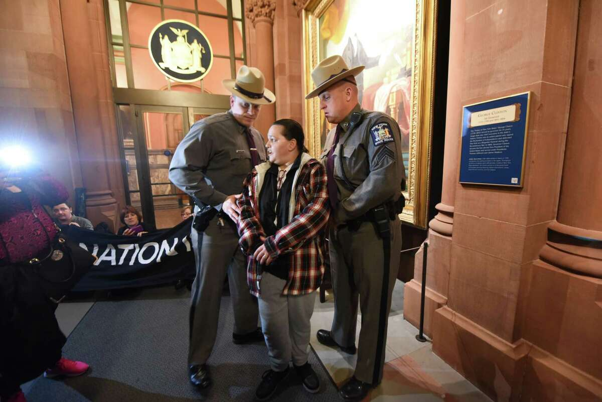 State Police remove an activist during a demonstration in support of the homeless outside Gov. Cuomo?'s office on Monday, March 27, 2017, at the Capitol in Albany, N.Y. People representing over 88,000 homeless New Yorkers blocked passageways inside the Capitol. They are calling for passage of progressive tax policies that would help state homeless issues. The protest was planned by the Albany Can End Homelessness in New York State campaign comprised of 43 faith and community groups across the state. (Will Waldron/Times Union)