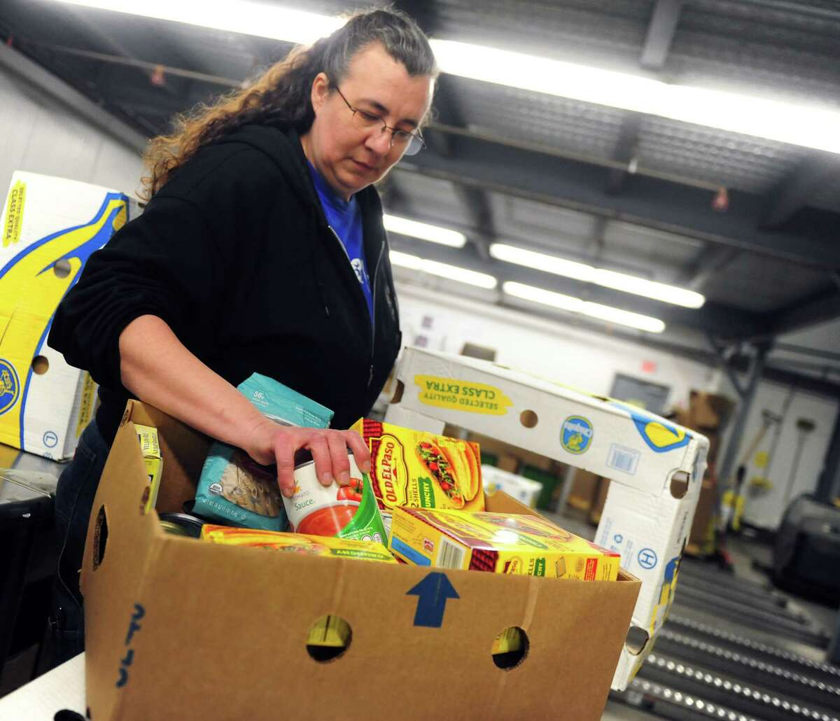 Tammie Racine sorts through boxes in the salvage sorting room of the Regional Food Bank in Albany, N.Y. on March 27, 2017. (Robert Downen/Times Union)