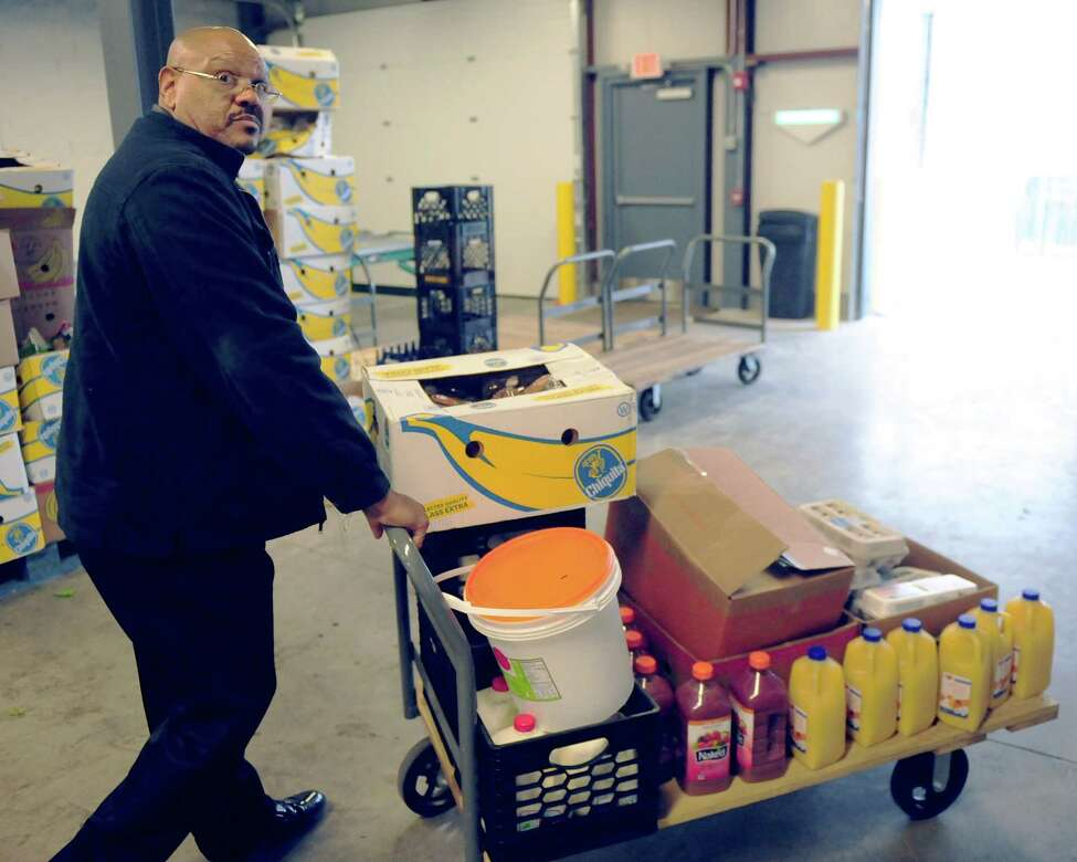 Elwood Powell Jr., regional director of 820 River Street Inc., wheels out food that he'll give to the roughly 75 people in drug addiction recovery programs. The organizaition is one of many that rely on the Regional Food Bank, in Colonie, N.Y. for fresh food and other materials. (Robert Downen/Times Union)