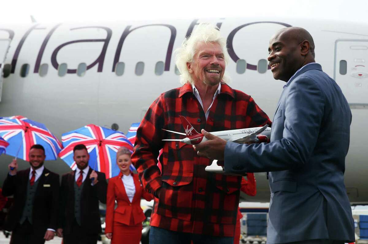 Virgin founder Sir Richard Branson gives a model plane to Lance Lyttle, managing director of the Port of Seattle, after arriving on a Boeing 787-9 for an event announcing Virgin Atlantic's new non-stop daily Seattle to London flights, Monday, March 27, 2017.