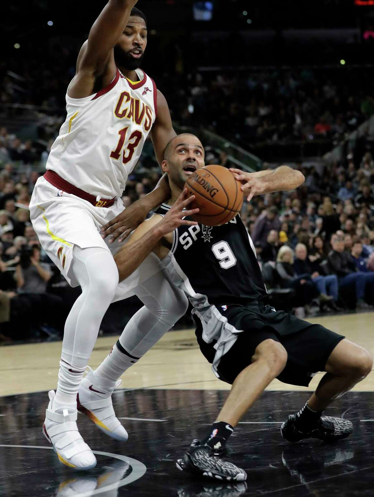San Antonio Spurs guard Tony Parker (9) is pressured by Cleveland Cavaliers center Tristan Thompson (13) as he tries to score during the second half of an NBA basketball game, Tuesday, Jan. 23, 2018, in San Antonio. San Antonio won 114-102. (AP Photo/Eric Gay)