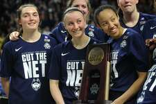 UConn seniors Tierney Lawlor, of Ansonia, and Saniya Chong hold the Regional Championship Trophy surrounded by their teammates following their victory over Oregon in the NCAA Women's Basketball Regional Final game at the Webster Bank Arena in Bridgeport, Conn. on Monday, March 27, 2017.