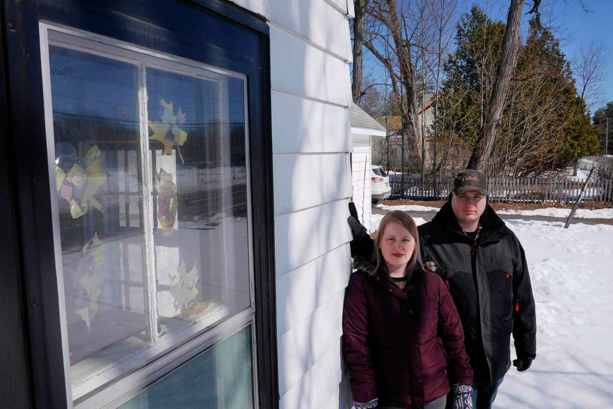 Dana Parzych, left, and her husband Jeremy Parzych pose outside their home on Thursday, March 23, 2017, in Gansevoort, N.Y. The couple plans to try and sell their home, which they purchased in February of 2016 because the neighboring property, seen in the background, is where a Dollar General store will be built. (Paul Buckowski / Times Union)
