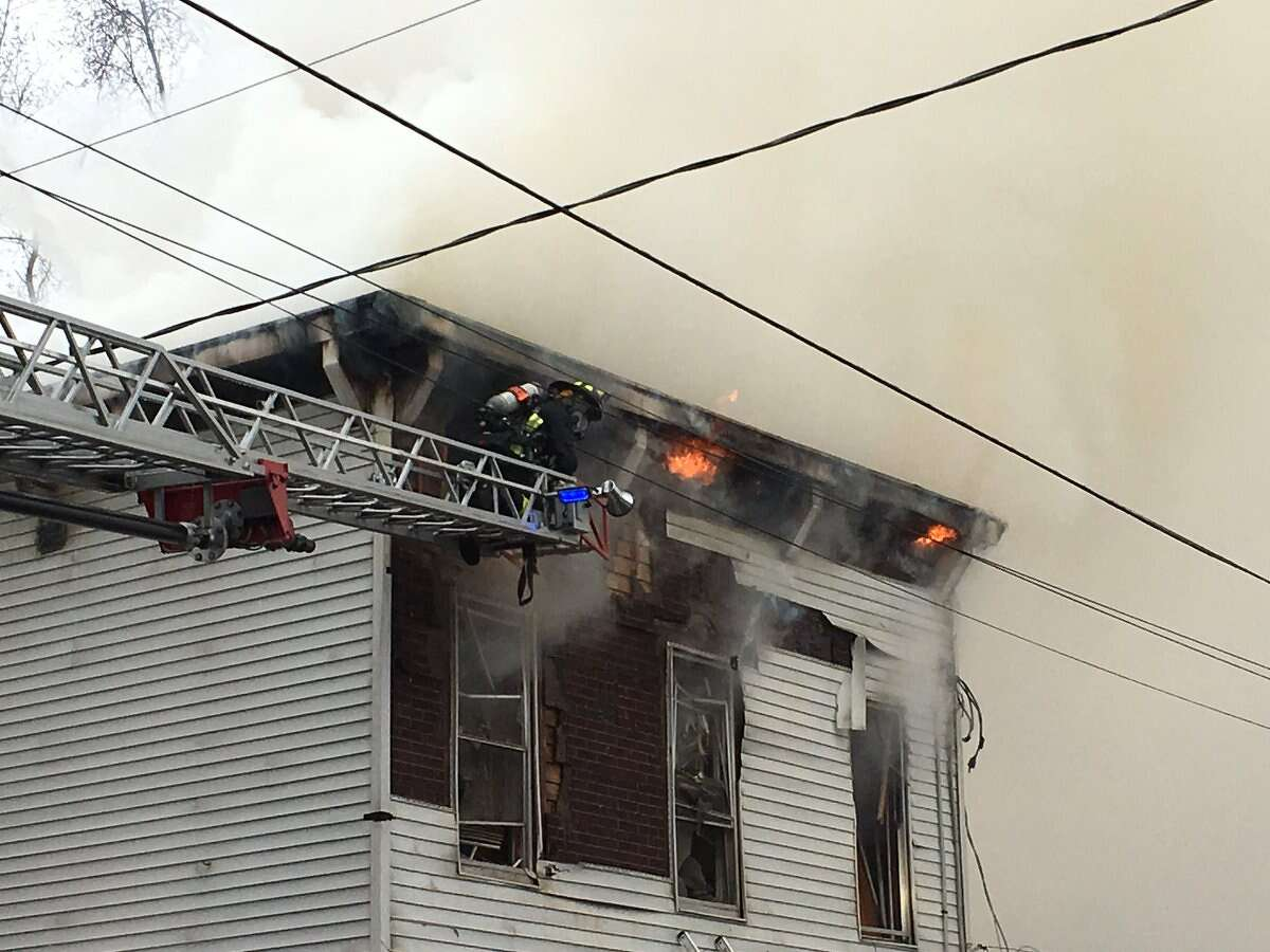 The fire at 15 Washington Ave., in Waterford, spreads into the attic late Monday morning. (Emily Masters / Times Union)
