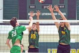 Metro-East Lutheran's Caleb Cope, middle, and Braden Woolsey, right, go up for a block during Monday's home match against Mehlville.