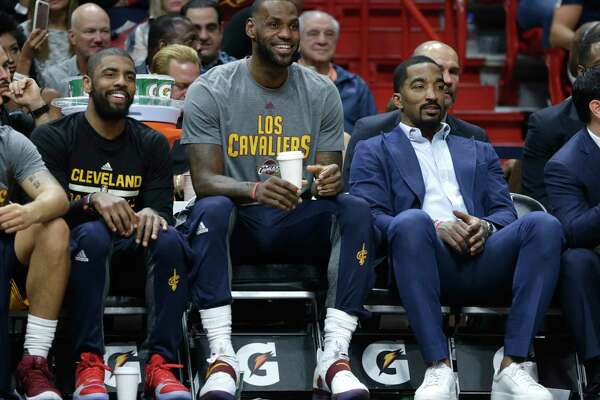 Cleveland Cavaliers' Kyrie Irving, left, LeBron James, center, and J.R. Smith, right, watch from the bench during the first half of an NBA basketball game against the Miami Heat, Saturday, March 4, 2017, in Miami. (AP Photo/Lynne Sladky) ORG XMIT: AAA107