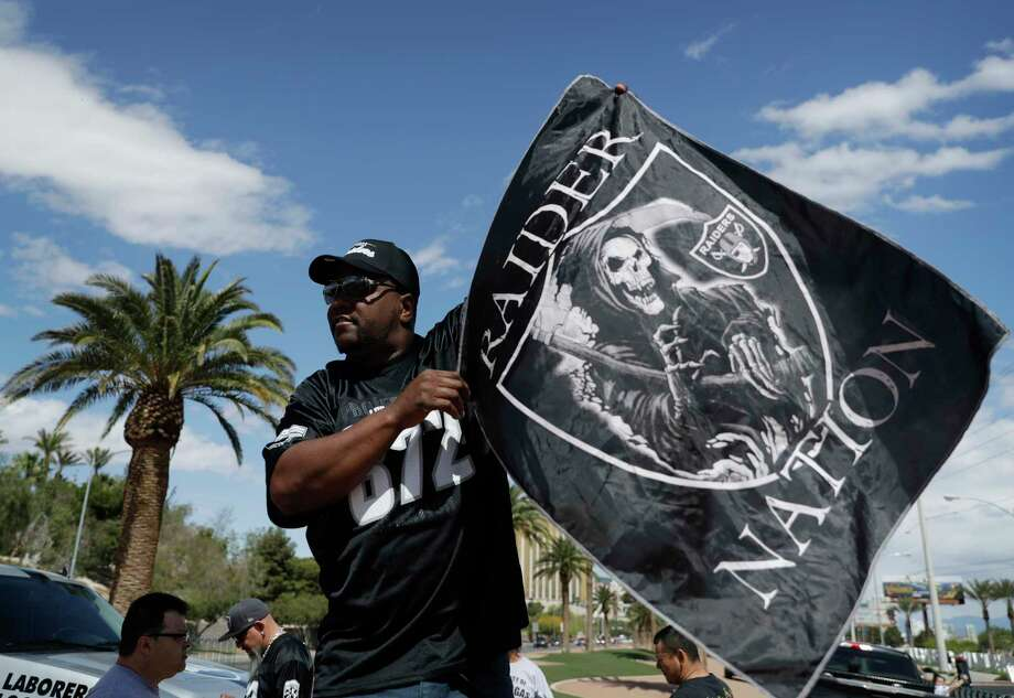 Ken Mclin holds up a Raiders banner Monday, March 27, 2017, in Las Vegas. NFL team owners approved the move of the Raiders to Las Vegas in a vote at an NFL football annual meeting in Phoenix. (AP Photo/John Locher) ORG XMIT: NVJL102 Photo: John Locher / Copyright 2017 The Associated Press. All rights reserved.
