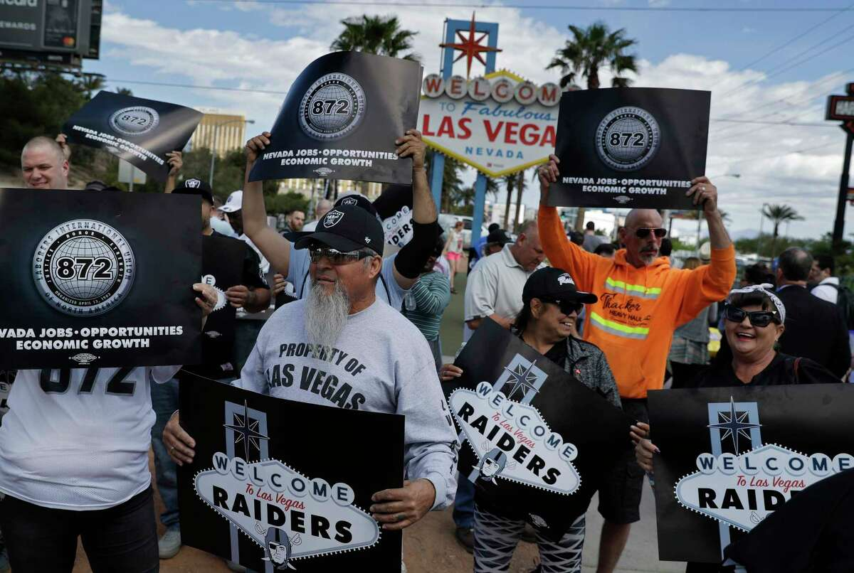 Members of a laborers union celebrate the Raiders move, Monday, March 27, 2017, in Las Vegas. NFL team owners approved the move of the Raiders to Las Vegas in a vote at an NFL football annual meeting in Phoenix. (AP Photo/John Locher) ORG XMIT: NVJL103