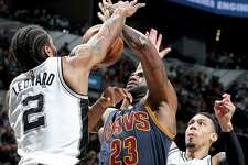 Cleveland Cavaliers' LeBron James is defended by San Antonio Spurs' Kawhi Leonard and Danny Green during second half action Monday March 27, 2017 at the AT&T Center.