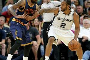Spurs' Kawhi Leonard looks for room around the Cleveland Cavaliers' Kyrie Irving during second half action on March 27, 2017 at the AT&T Center.
