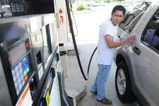 Efrain Gordillo of Stamford keeps an eye on the pump while putting gas into his vehicle at the BP station at 1324 E. Putnam Ave. in Old Greenwich, Wednesday, July 17, 2013. Gordillo said he now pays $90 to fill-up his SUV. The prices at the station range from $4.15 to $4.49 per gallon.