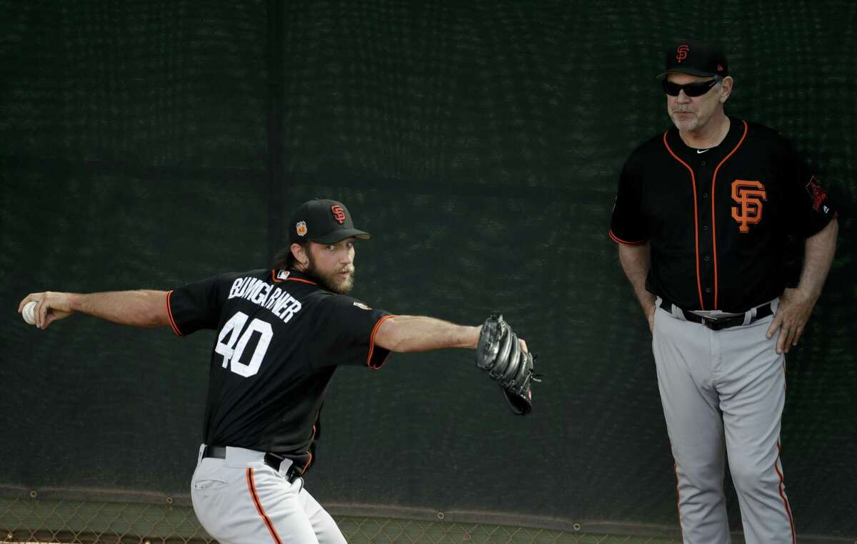 San Francisco Giants manager Bruce Bochy, right, watches as starting pitcher Madison Bumgarner throws during spring baseball practice in Scottsdale, Ariz., Tuesday, Feb. 14, 2017. (AP Photo/Chris Carlson)