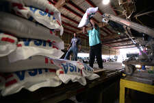Joseph Long tosses 110 pound bags of rice onto the back of a truck at Beaumont Rice Mills on Wednesday. The company is celebrating its 125th year operating is Beaumont.  Photo taken Wednesday, March 22, 2017 Guiseppe Barranco/The Enterprise