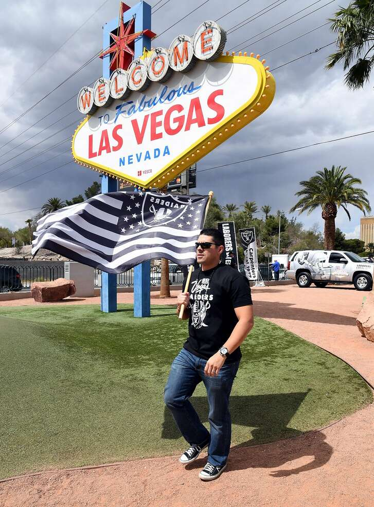 LAS VEGAS, NV - MARCH 27:  Oakland Raiders fan Matt Gutierrez of Nevada carries a Raiders flag in front of the Welcome to Fabulous Las Vegas sign after National Football League owners voted 31-1 to approve the team's application to relocate to Las Vegas during their annual meeting on March 27, 2017 in Las Vegas, Nevada. The Raiders are expected to begin play no later than 2020 in a planned 65,000-seat domed stadium to be built in Las Vegas at a cost of about USD 1.9 billion.  (Photo by Ethan Miller/Getty Images)