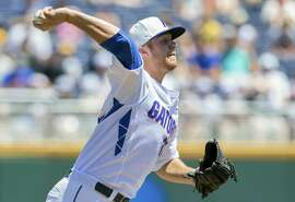 Florida starting pitcher Logan Shore (32) throws to first base in the first inning of an NCAA College World Series baseball game against Virginia at TD Ameritrade Park in Omaha, Neb., Friday, June 19, 2015. (AP Photo/Nati Harnik)