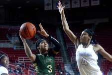 Legacy Christian Academy's Alexis Morris puts up her shot against the efforts of Lufkin's Ivie Massie as they vie for the YMBL trophy during Saturday's tournament finals at the Montagne Center. Photo taken Saturday, December 3, 2016 Kim Brent/The Enterprise