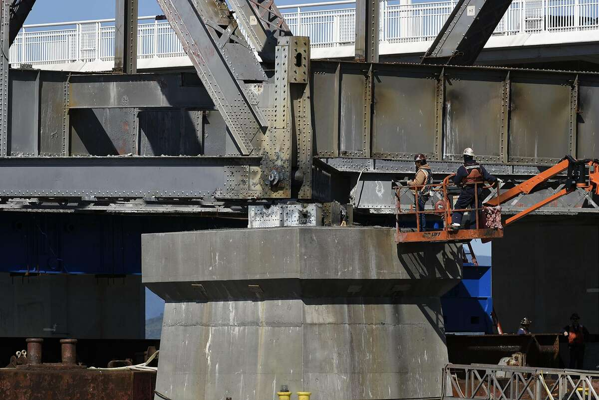 Workers keep a close eye as the final steel truss span of the Old Bay Bridge is floated off of it's moorings, in Oakland, CA, on Tuesday March 28, 2017.
