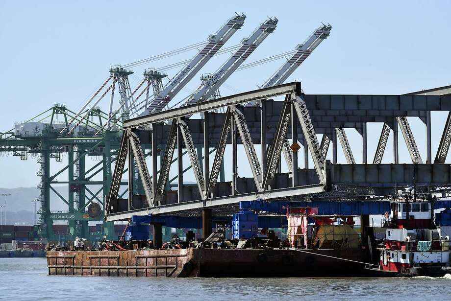 Port of Oakland shipping cranes are seen in the background as the final steel truss span of the Old Bay Bridge is floated away on barges, in Oakland, CA, on Tuesday March 28, 2017. Photo: Michael Short, Special To The Chronicle