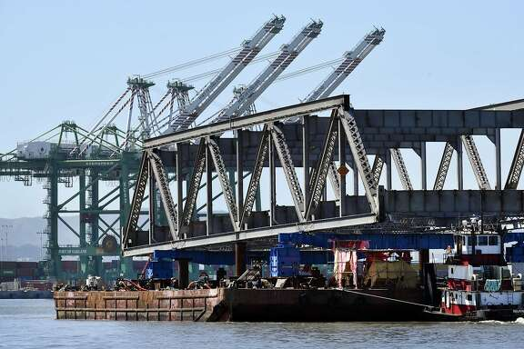 Port of Oakland shipping cranes are seen in the background as the final steel truss span of the Old Bay Bridge is floated away on barges, in Oakland, CA, on Tuesday March 28, 2017.
