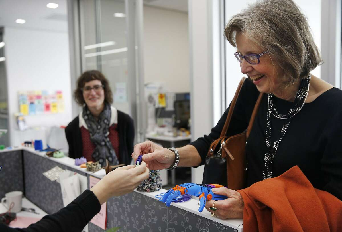 Karen Bosch Cobb, right, from Veterans Connect @ the Library marvels at a prosthetic hand as Learning Differences Librarian Laura Lay hands her fingers at the Bridge at Main Learning and Literacy Center Jan. 21, 2016 in the main San Francisco Public Library in San Francisco, Calif. The Center has had the 3D printer for about a year. They use it to teach digital literacy to people of all ages and recently started printing simple prosthetic hands they can donate to children as well as use them as examples to their students of what a 3D printer can do.