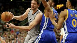 Spurs' Pau Gasol looks to pass around the Golden State Warriors' Kevon Looney (left) and Patrick McCaw during second half action on March 11, 2017 at the AT&T Center.