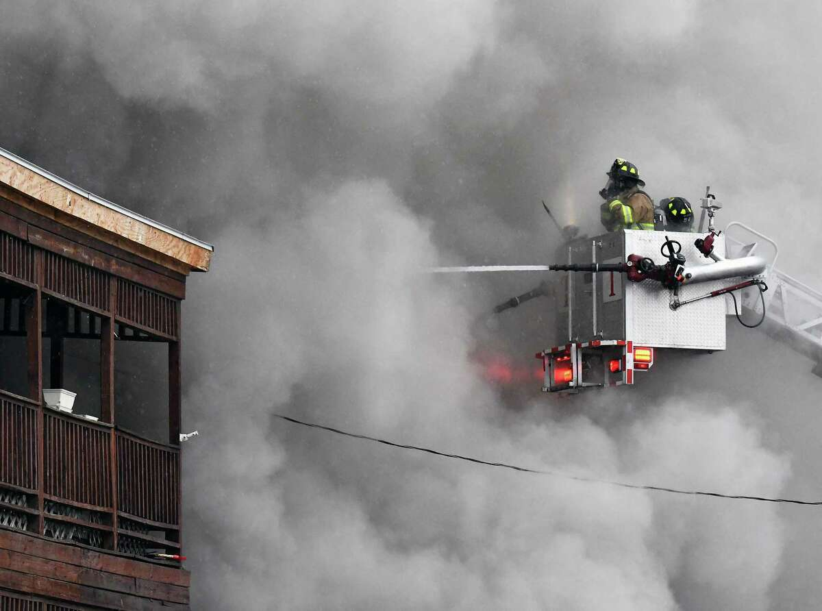 Firefighters atop an aerial ladder are engulfed in smoke as they battle a house fire at 292 Saratoga Street Tuesday March 28, 2017 in Cohoes, NY. (John Carl D'Annibale / Times Union)
