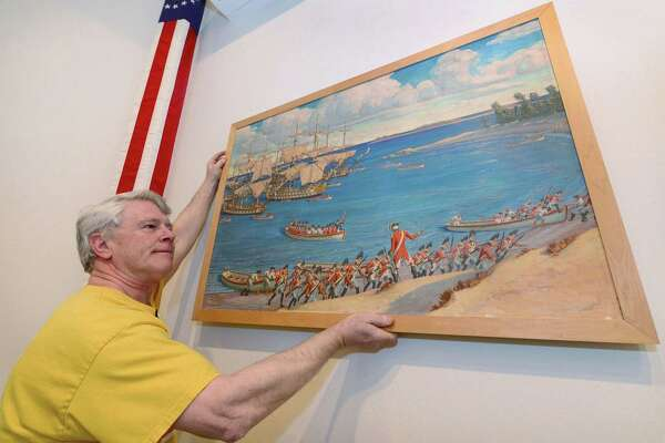 Ed Hynes, curator of the Westport Historical Society's Danbury Raid exhibit, The British are Coming!, hangs a depiction of the landing at Compo Beach for the exhibit Tuesday, March 28, 2017, at the Westport Historical Society in Westport, Conn. The Westport Historical Society and the City of Norwalk declared April American Revolution Month in recognition of the Danbury raid of April, 1777. The exhibit, The British are Coming!, will open April 2nd.
