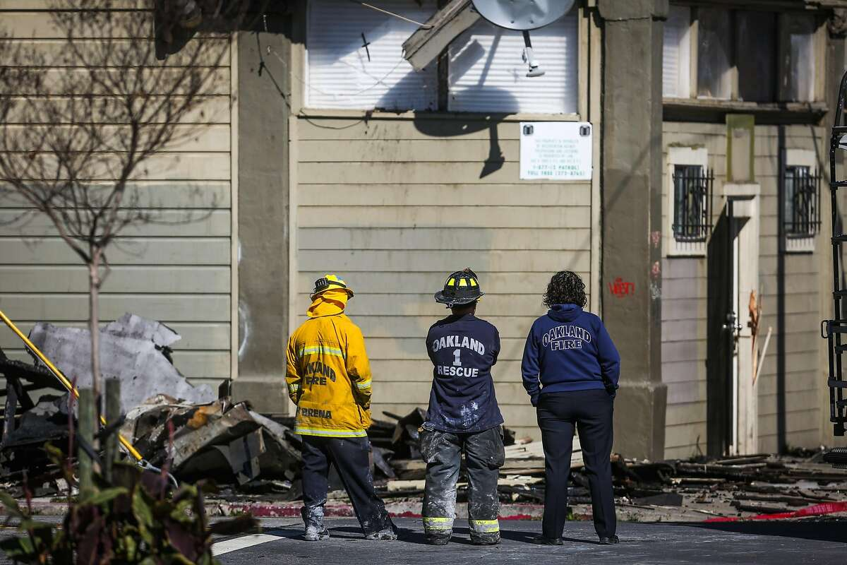 Oakland Fire personnel look at the remains of an apartment complex which was destroyed in a four-alarm fire on San Pablo Avenue in Oakland, California, on Tuesday, March 28, 2017.