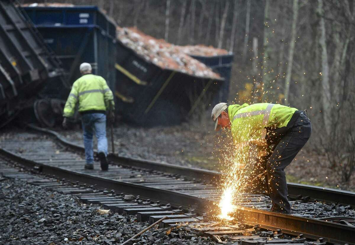 A Housatonic Railroad worker torches a section of track Tuesday by a train that derailed Monday night near the crossing of Rooster Tail Hollow and its intersection with River Road in New Milford.