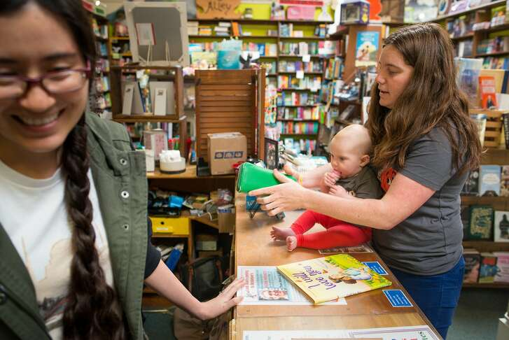 Kathy Ellen Davis holds her daughter Rosemary Gratien, and while Suzi Hough rings up her purchase in Hicklebee's Childrens Books in San Jose, Calif. on March 28, 2017.  San Jose businesses like Hicklebee's are unsure how the .5% sales tax increase, which goes into effect April 1st, will impact them.