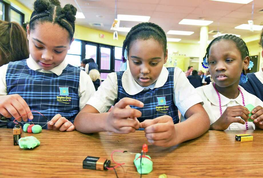 Brighter Choice Charter Elementary fifth graders Naja'hry Coles, left, Kh'mya Brooks, and Zhy'A Codrington, right, experiment with conductive dough during a visit to their school by SUNY Polytechnic Institute for a series of hands-on educational programs Tuesday March 28, 2017 in Albany, NY.  (John Carl D'Annibale / Times Union) Photo: John Carl D'Annibale / 20040080A