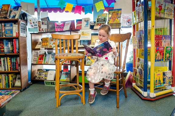 Harper Eastman, age 4, reads from a Disney book she found on the shelves of Hicklebee's Childrens Books in San Jose, Calif. on March 28, 2017.  San Jose businesses like Hicklebee's are unsure how the .5% sales tax increase, which goes into effect April 1st, will impact them.