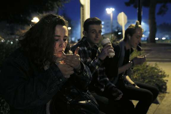 Natalie Richards, 19, smokes a cigarette as she sits with her friends Ben Rose, center, and Chase Melich, right, in a Designated Smoking Area at San Francisco State University as supervisors consider a plan to raise the purchasing age for tobacco products to 21 in San Francisco, Calif., on Monday, February 29, 2016.