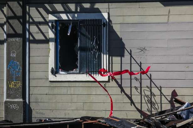 A broken window is seen in an apartment complex that was destroyed in a four-alarm fire yesterday on San Pablo Avenue in Oakland, California, on Tuesday, March 28, 2017.