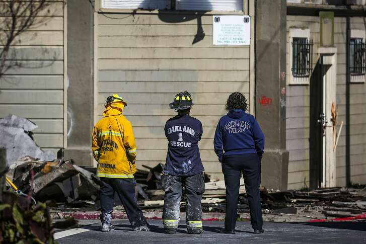 Oakland Fire personnel look at the remains of an apartment complex which was destroyed in a four-alarm fire yesterday on San Pablo Avenue in Oakland, California, on Tuesday, March 28, 2017.